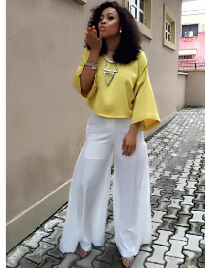 Blowing kisses in a silk yellow blouse and palazzo trousers