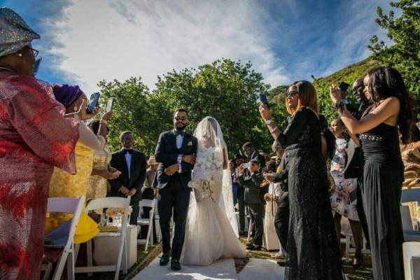 Adesua being walked down the aisle .