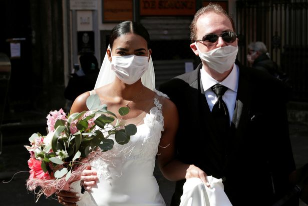 Fernandes and Salgado kiss through protective face masks during their wedding ceremony in Italy